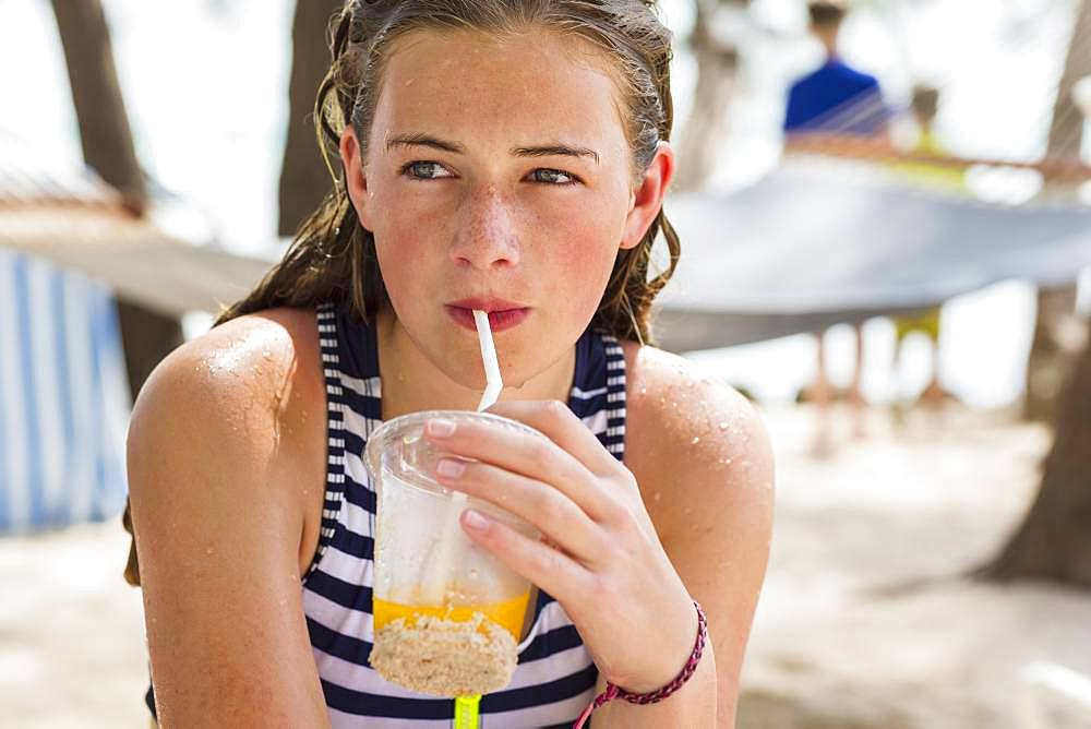 A teenage girl resting in hammock sipping fruit drink, Grand Cayman, Cayman Islands