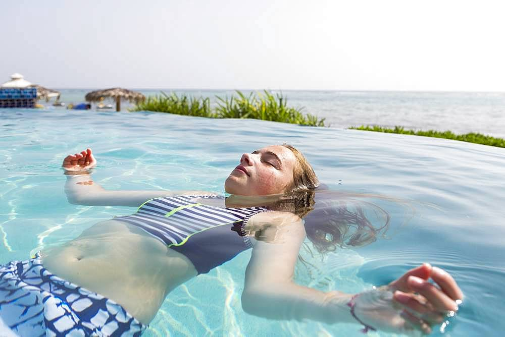A teenage girl floating in infinity pool, Grand Cayman, Cayman Islands