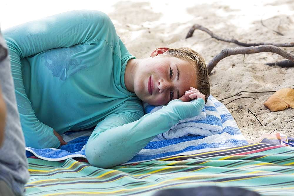 A teenage girl resting on a beach towel, Grand Cayman, Cayman Islands