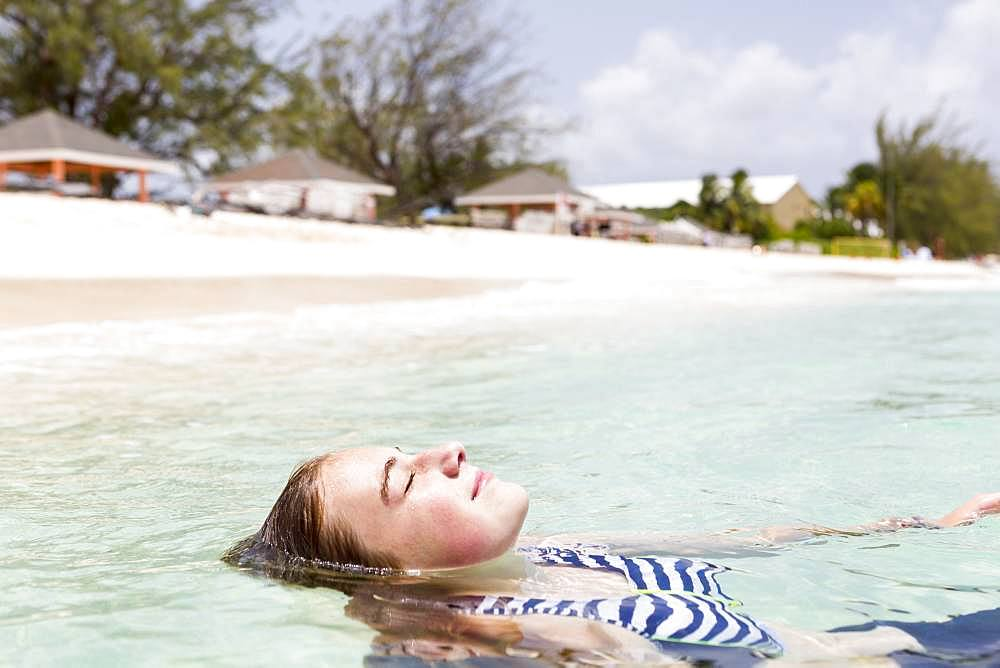 A teenage girl floating in the ocean, Grand Cayman, Cayman Islands