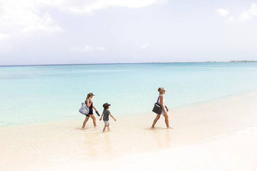 Mother and her children walking the beach, Grand Cayman, Cayman Islands