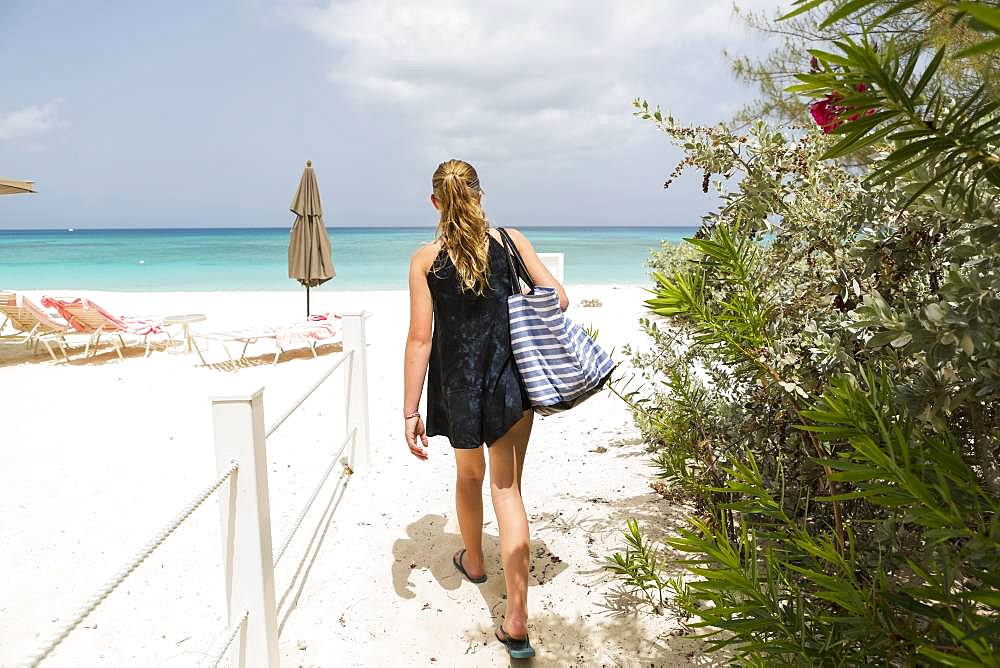 A teenage girl walking the beach, Grand Cayman, Cayman Islands