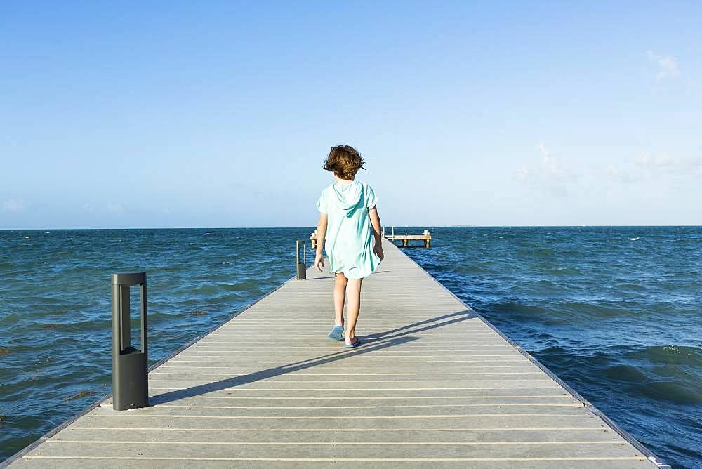 5 year old boy walking on a pier, view to the horizon, Grand Cayman, Cayman Islands