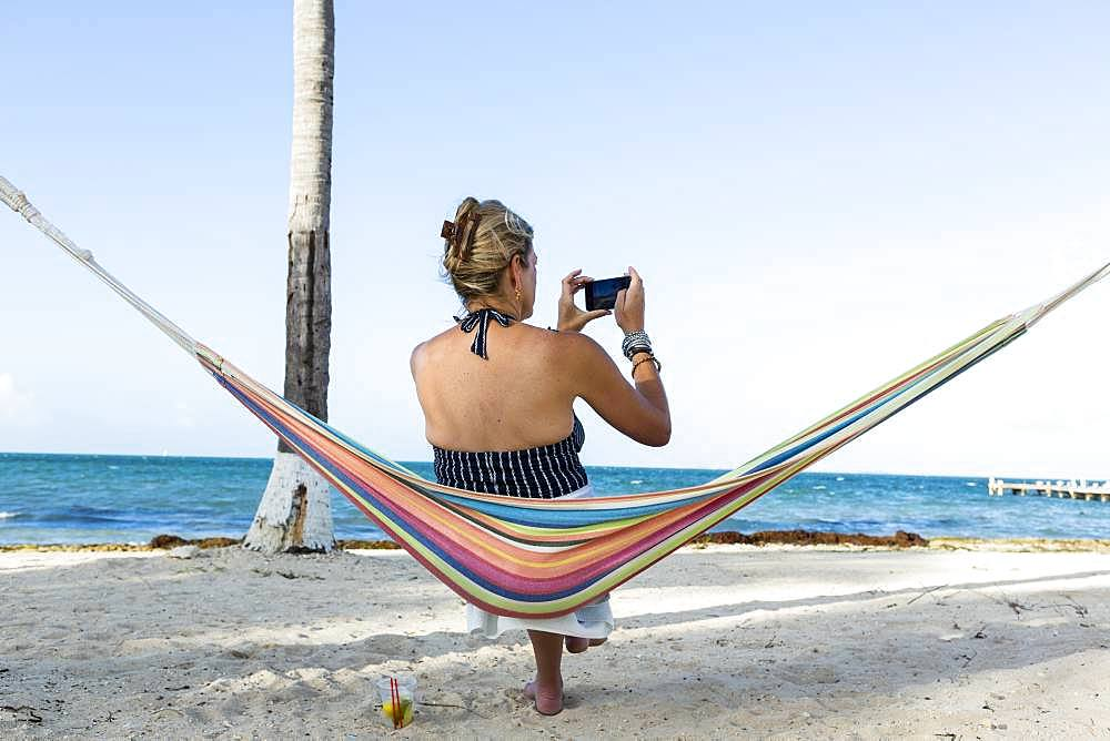 Woman resting in hammock taking picture with smart phone, Grand Cayman, Cayman Islands