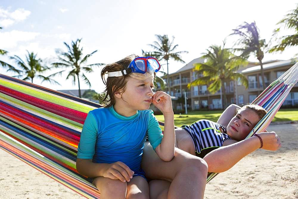 5 year old boy in hammock with his 13 year old sister, Grand Cayman, Cayman Islands