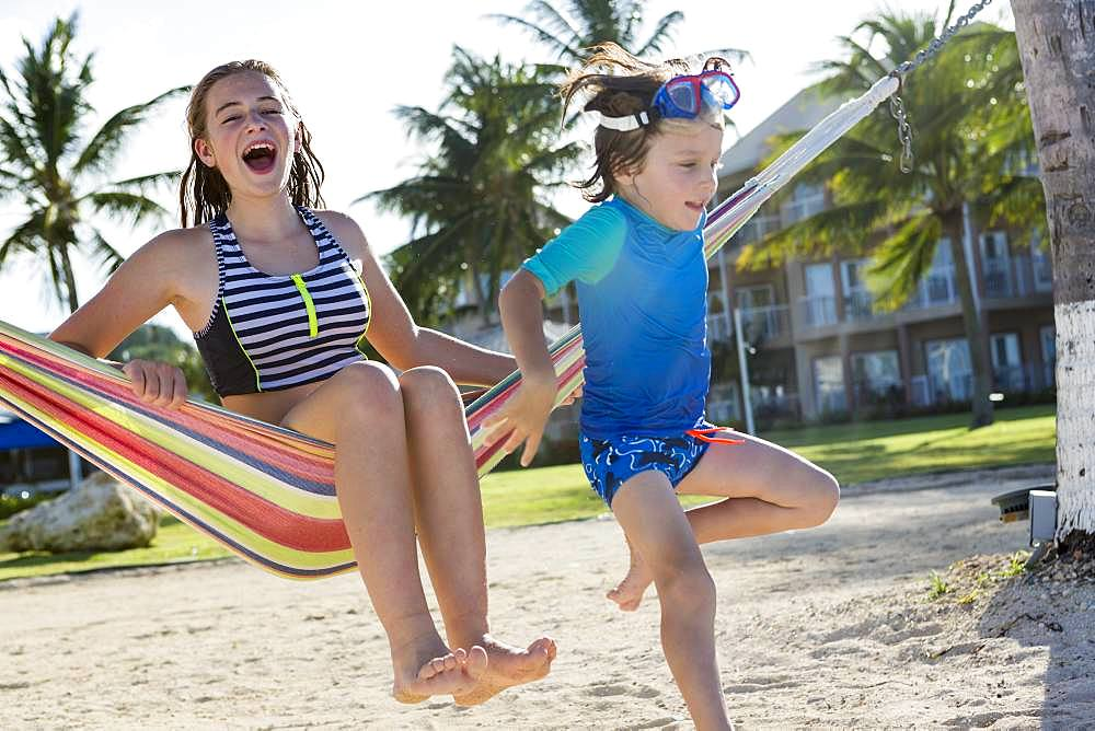 A teenage girl in hammock with her 5 year old brother, Grand Cayman, Cayman Islands