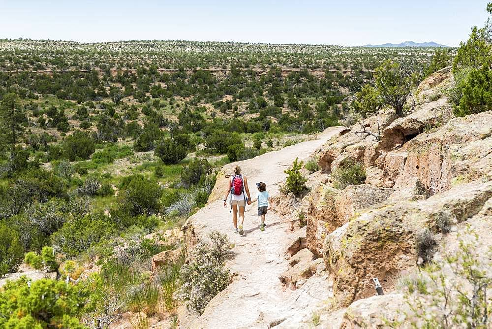 mother and her 5 year old son walking on a path in the New Mexico desert