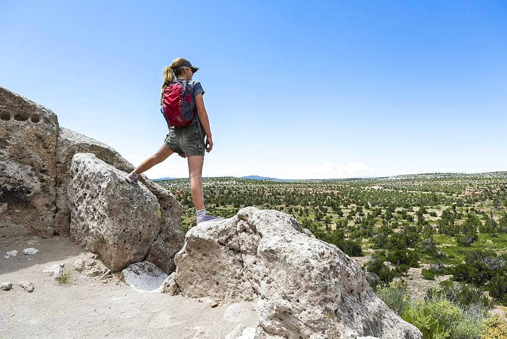 Rear view of teenage girl hiker overlooking desert vista at the Tsankawi Ruins