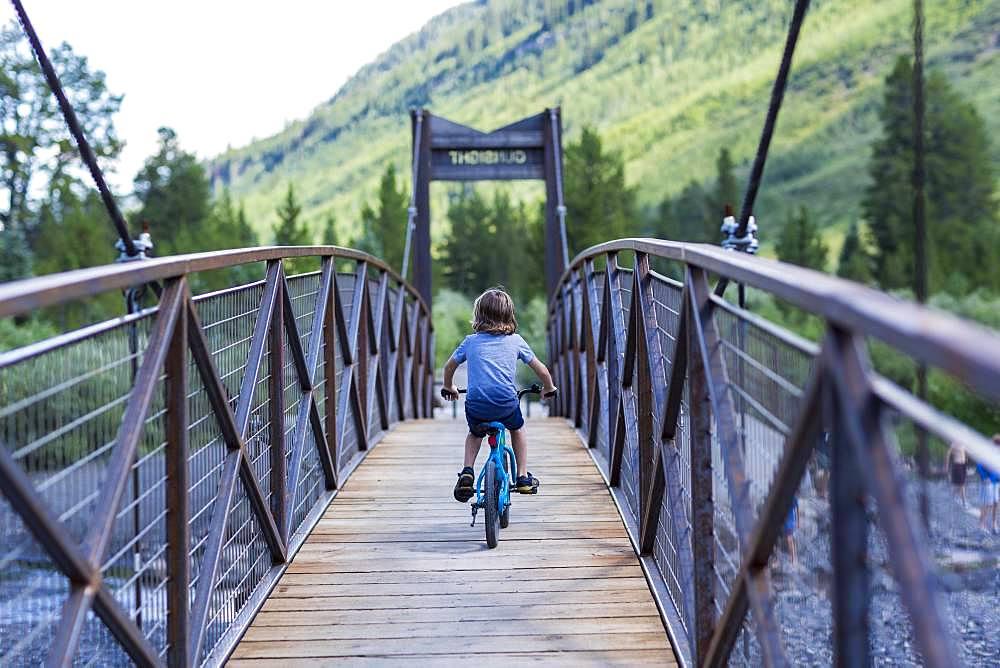 rear view of 5 year old boy on mountain crossing narrow bridge