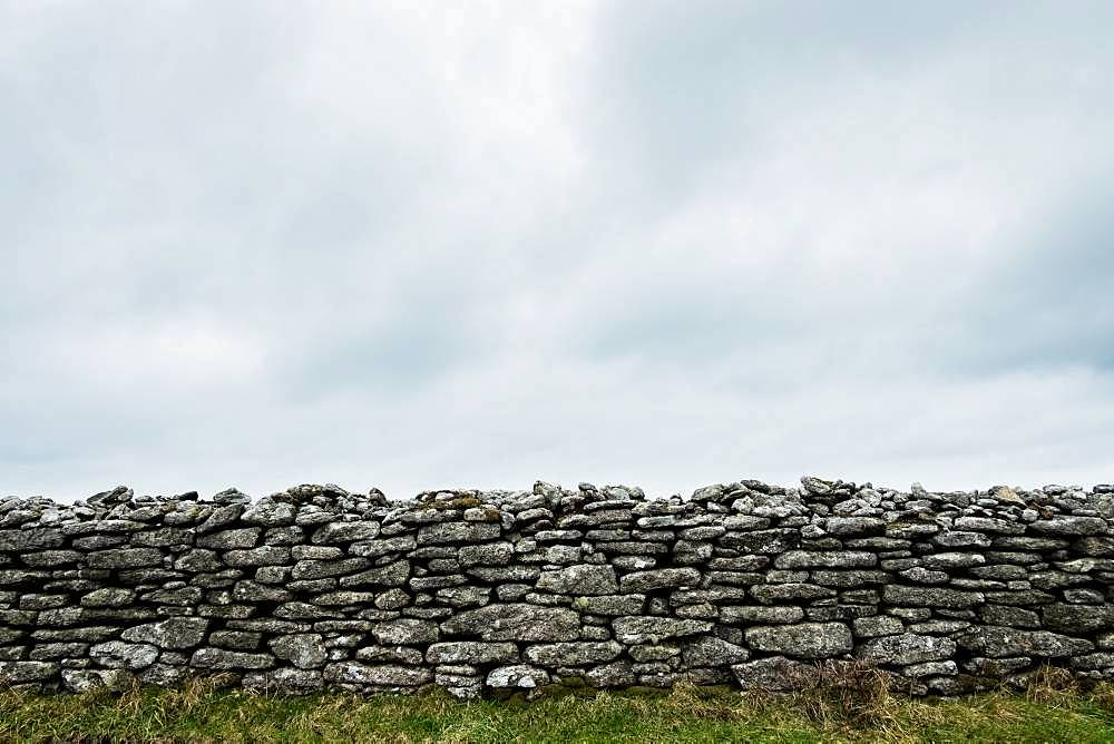View of old dry stone wall under a cloudy sky