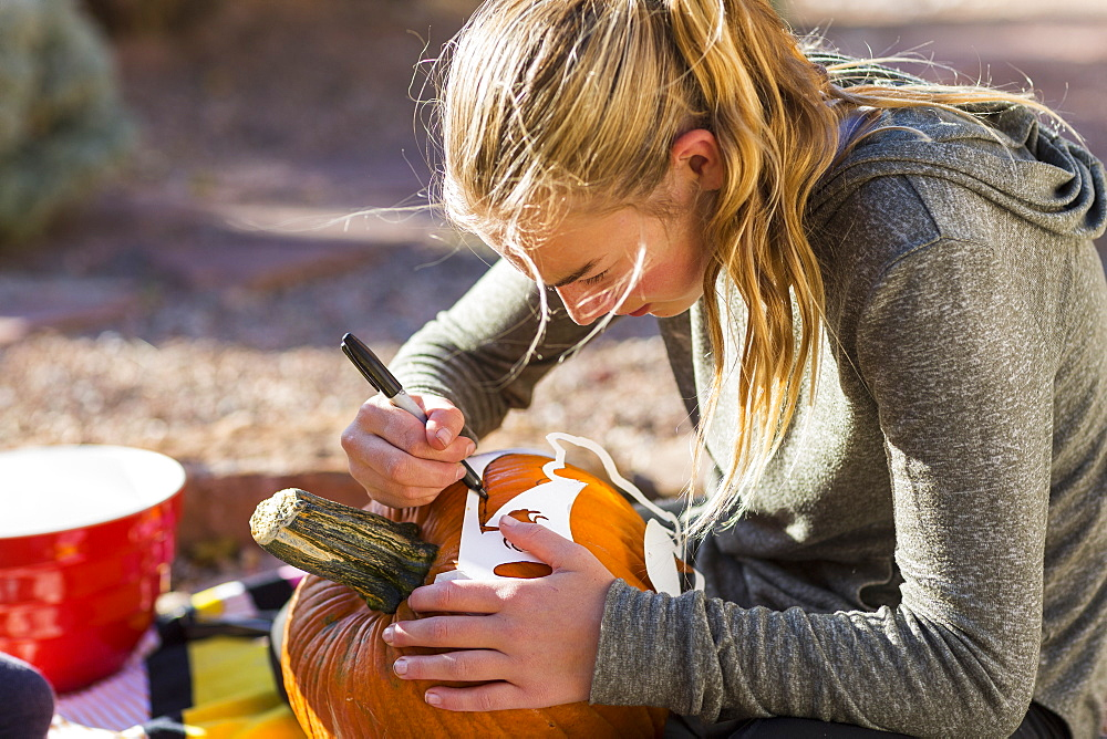 A teenage girl carving pumpkin outdoors at Halloween