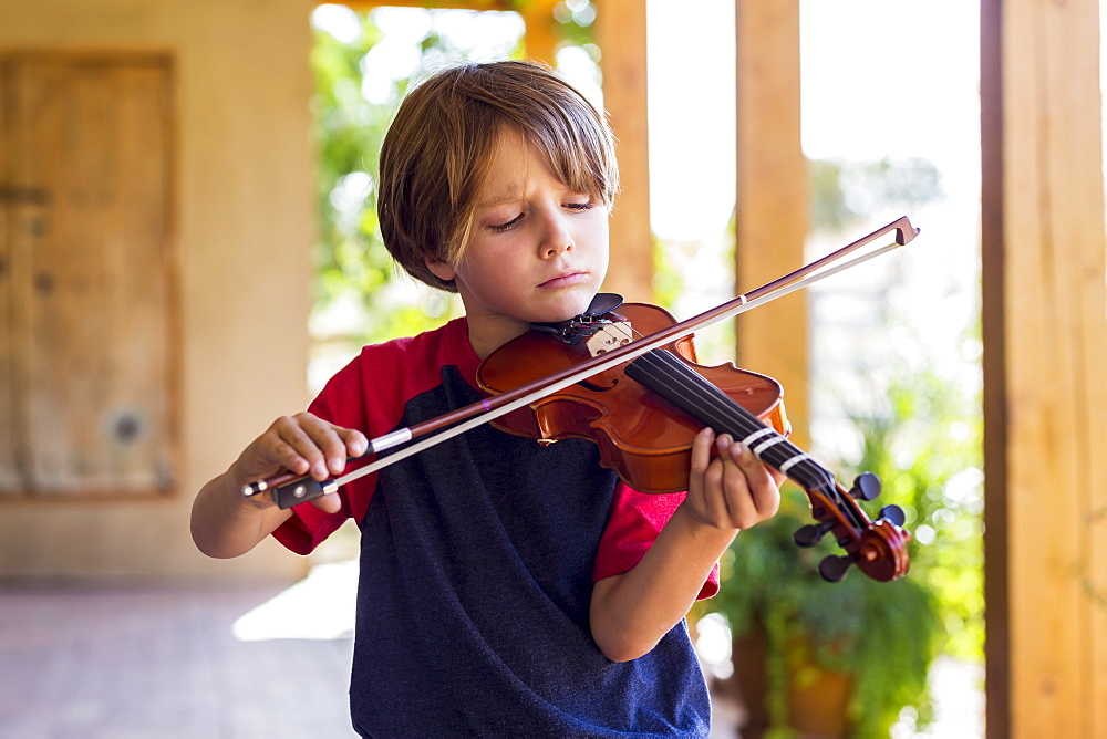 Six year old boy playing violin outside in garden