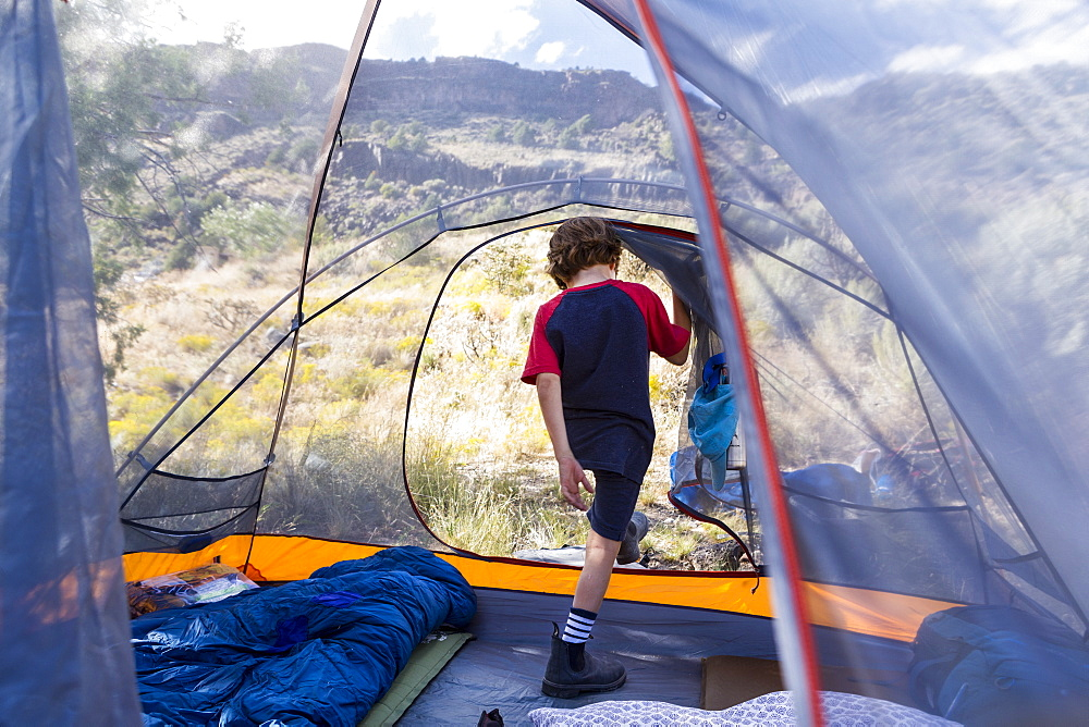 Six year old boy exiting tent in early morning light