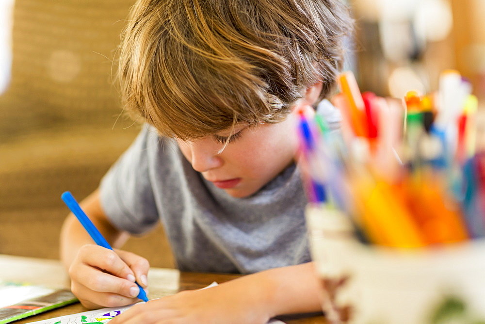 Six year old boy drawing amoung colorful pens - 1174-7131
