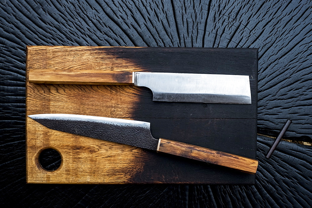 High angle close up of two handmade knives on wooden cutting board - 1174-7137