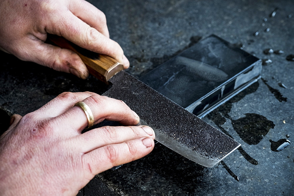High angle close up of person sharpening handmade knife on a whetstone