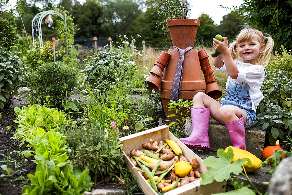 Smiling blond girl sitting in garden next to terracotta scarecrow, picking fresh vegetables