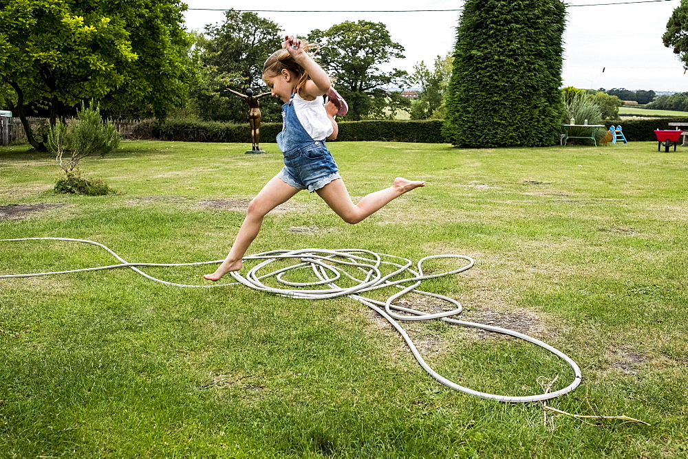 Girl wearing denim dungarees jumping over a garden hose on a lawn