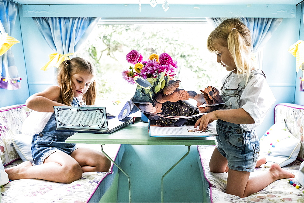 Two girls sitting at a table inside a blue caravan, playing