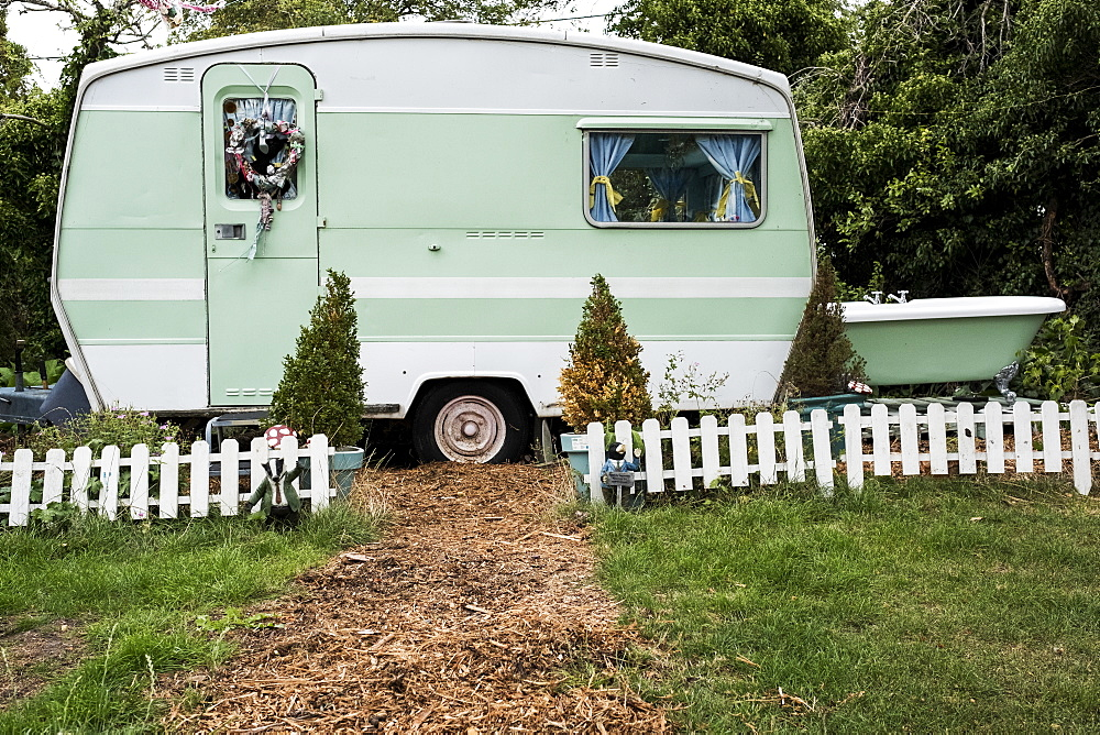White and green retro caravan parked at the end of a garden path behind low white picket fence
