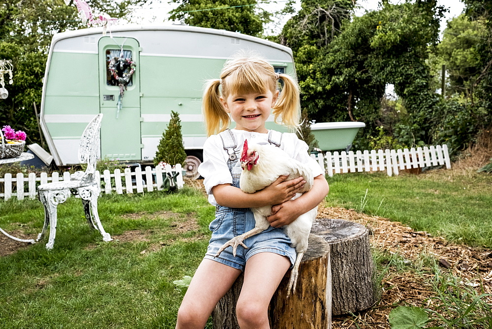 Blond girl sitting in garden holding white chicken, white and green retro caravan in background