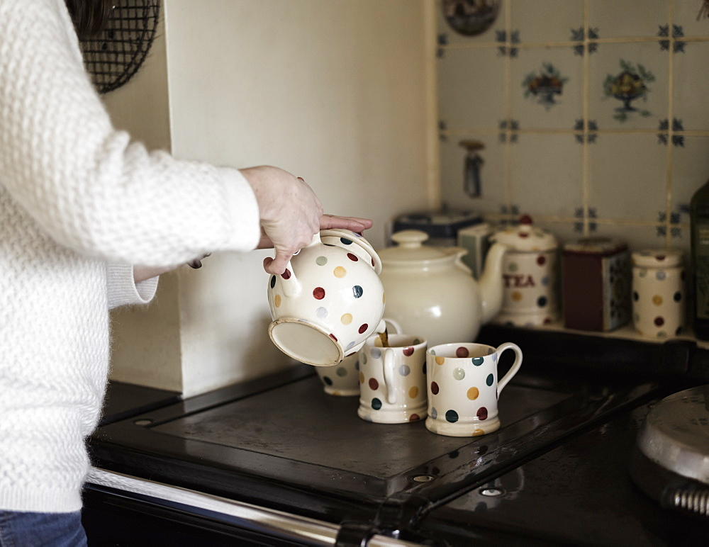 A woman pouring tea, by a range cooker. Using decorative china, Ringwood, Hampshire, England