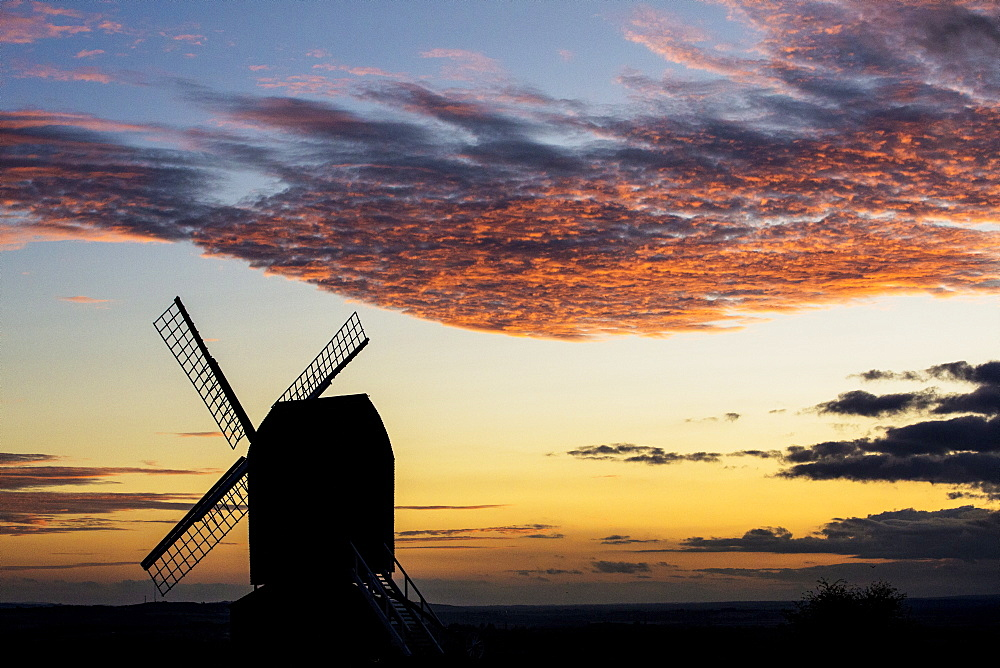 Windmill at sunset under a romantic cloudy sky