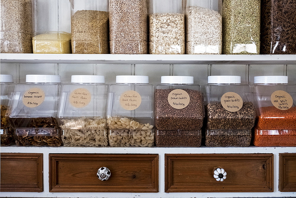 Close up of shelves with a selection of pasta, legumes and grains in glass jars - 1174-7174