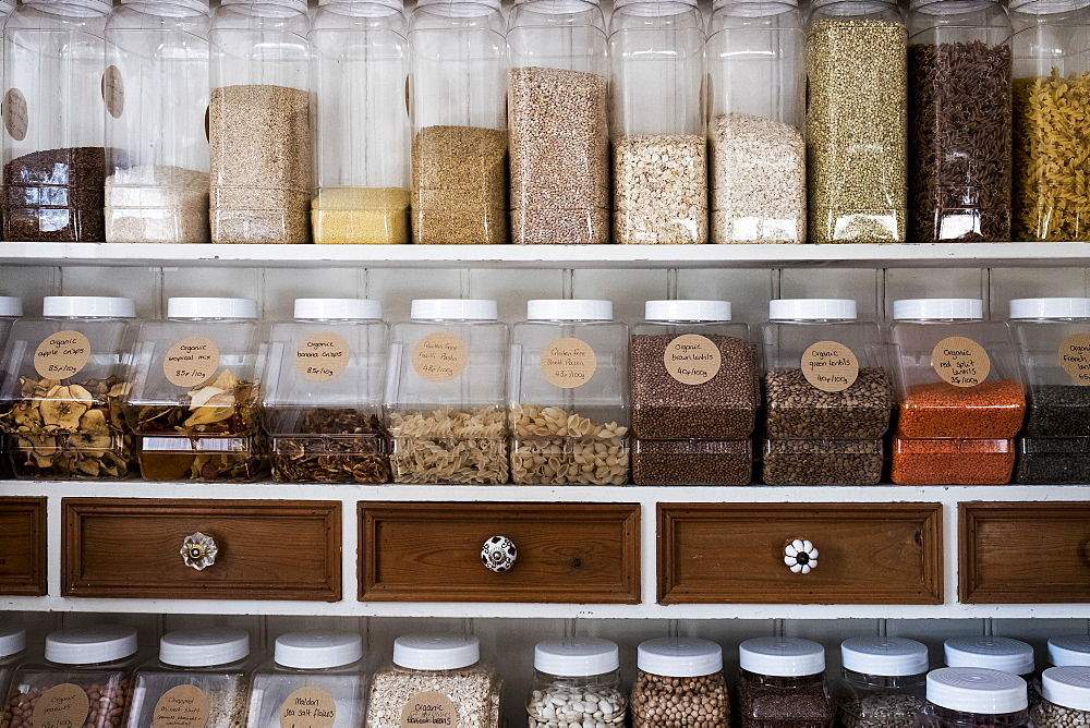 Close up of shelves with a selection of pasta, legumes and grains in glass jars - 1174-7176