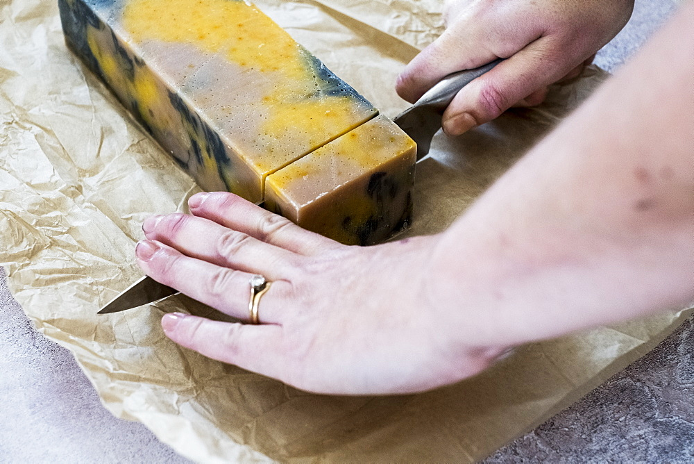 High angle close up person cutting yellow and black homemade bar of soap with kitchen knife
