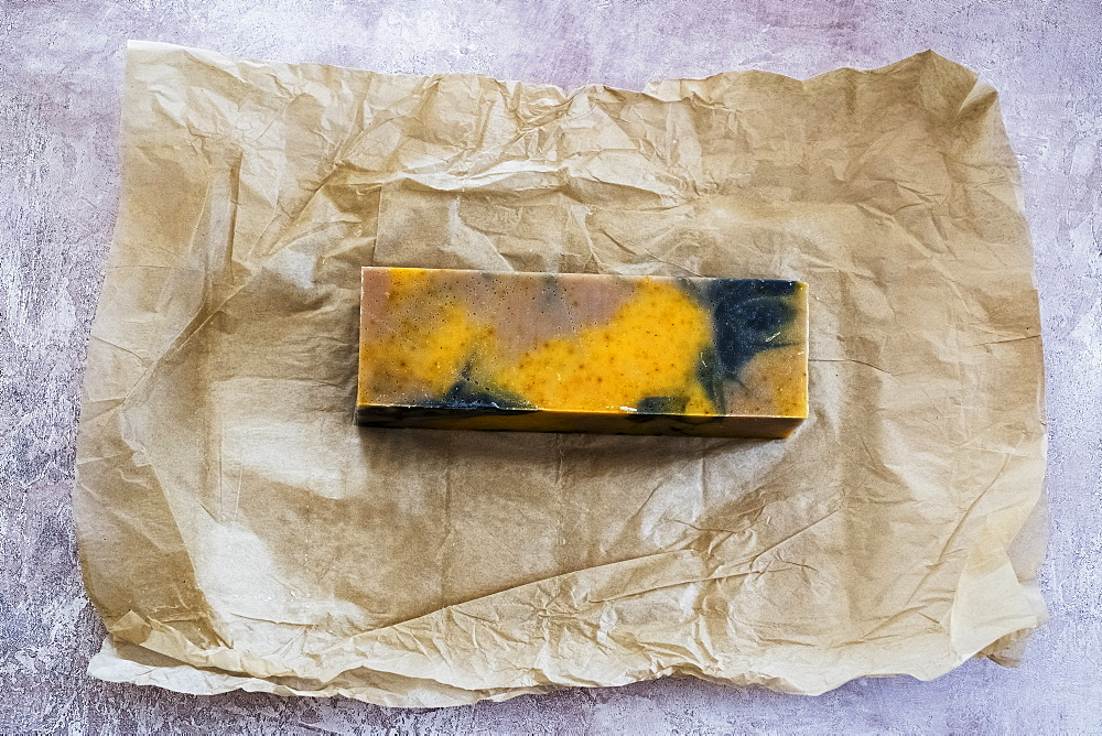 High angle close up of yellow and black homemade bar of soap on brown paper