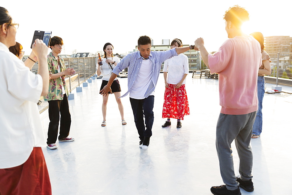 Group of young Japanese men and women dancing on a rooftop in an urban setting, Fukuoka, Kyushu, Japan