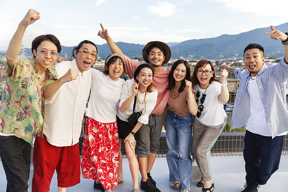 Smiling group of young Japanese men and women standing on a rooftop in an urban setting, Fukuoka, Kyushu, Japan