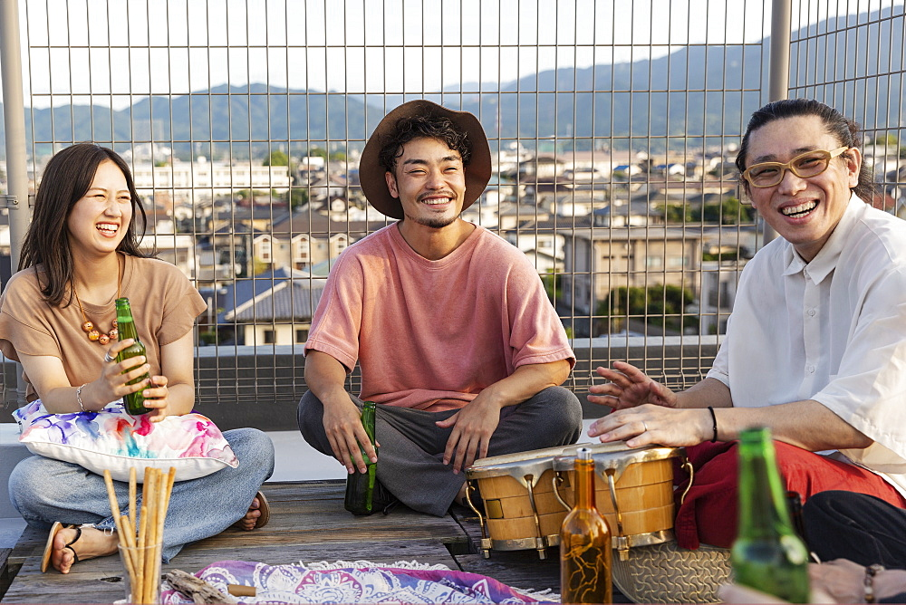 Smiling group of young Japanese men and women sitting on a rooftop in an urban setting, Fukuoka, Kyushu, Japan