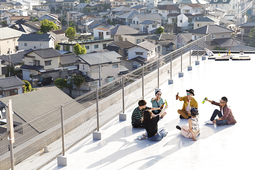 High angle view of group of young Japanese men and women sitting on a rooftop in an urban setting, Fukuoka, Kyushu, Japan