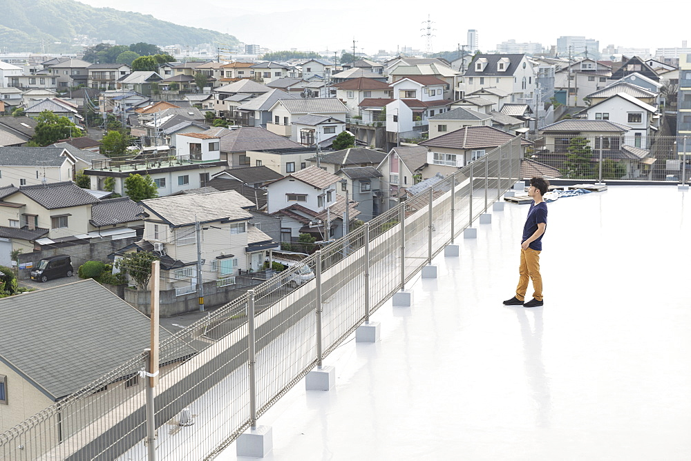 High angle view of Japanese man standing on a rooftop in an urban setting, Fukuoka, Kyushu, Japan