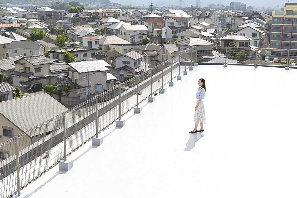 High angle view of Japanese woman standing on a rooftop in an urban setting, Fukuoka, Kyushu, Japan