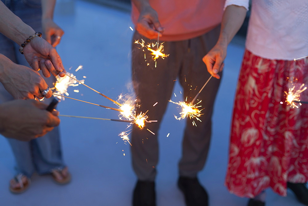 Group of young men and women with sparklers on a rooftop in an urban setting, Fukuoka, Kyushu, Japan