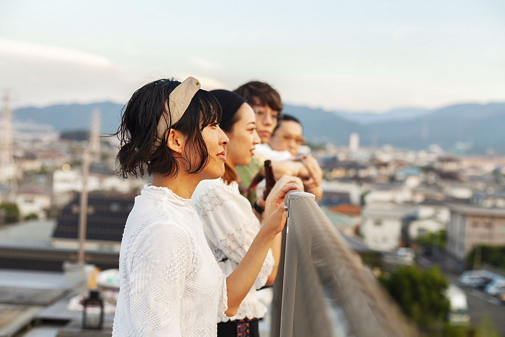 Group of young Japanese men and women standing on a rooftop in an urban setting, Fukuoka, Kyushu, Japan