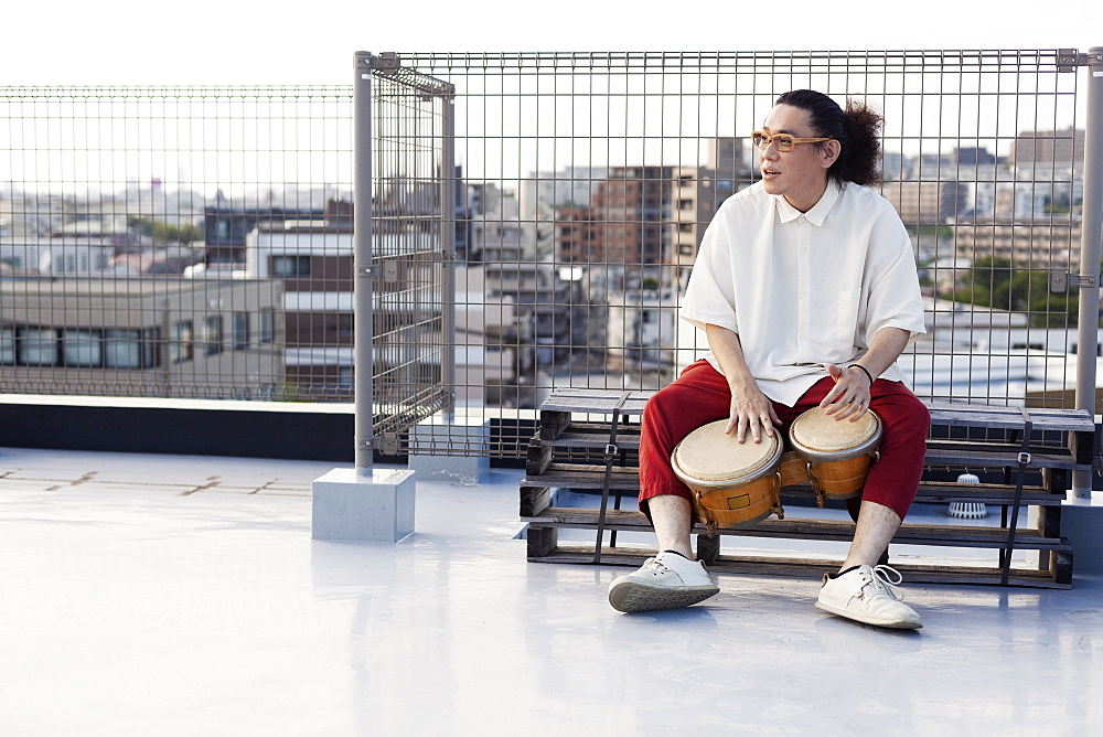 Japanese man sitting on a rooftop in an urban setting, playing drums, Fukuoka, Kyushu, Japan