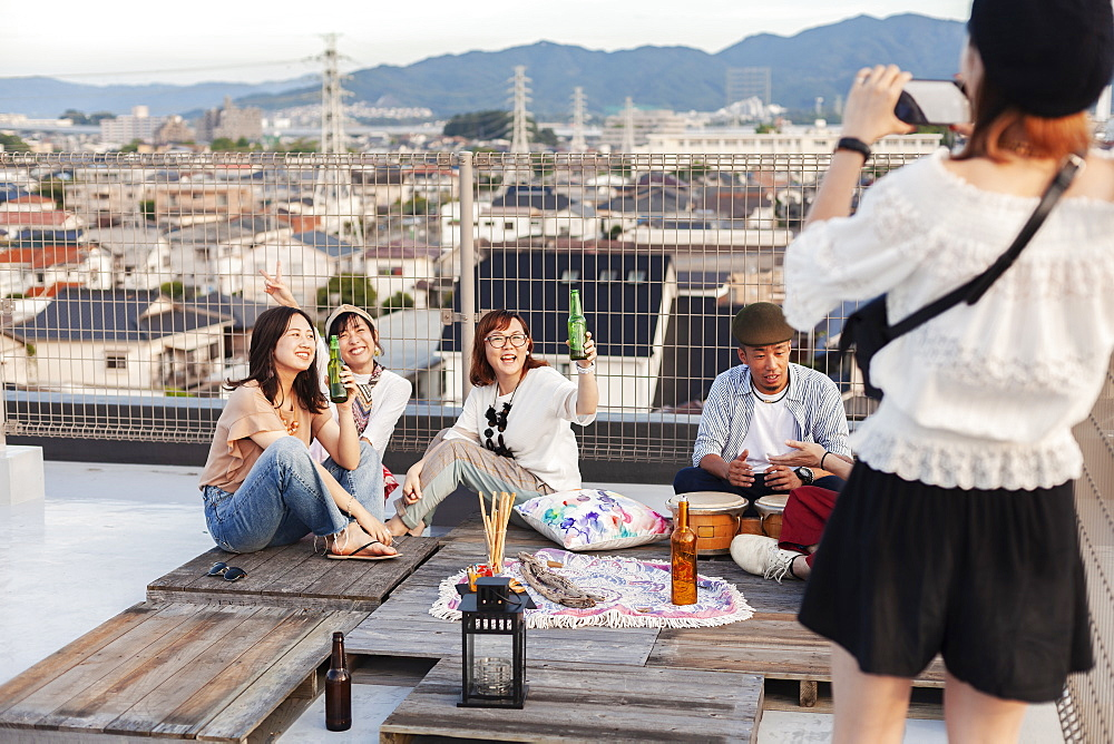 Smiling group of young Japanese men and women on a rooftop in an urban setting, Fukuoka, Kyushu, Japan