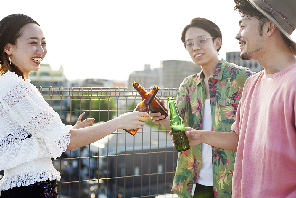Young Japanese men and woman standing on a rooftop in an urban setting, drinking beer, Fukuoka, Kyushu, Japan