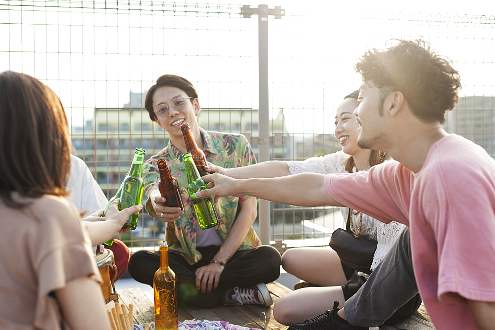Group of young Japanese men and women sitting on a rooftop in an urban setting, drinking beer, Fukuoka, Kyushu, Japan