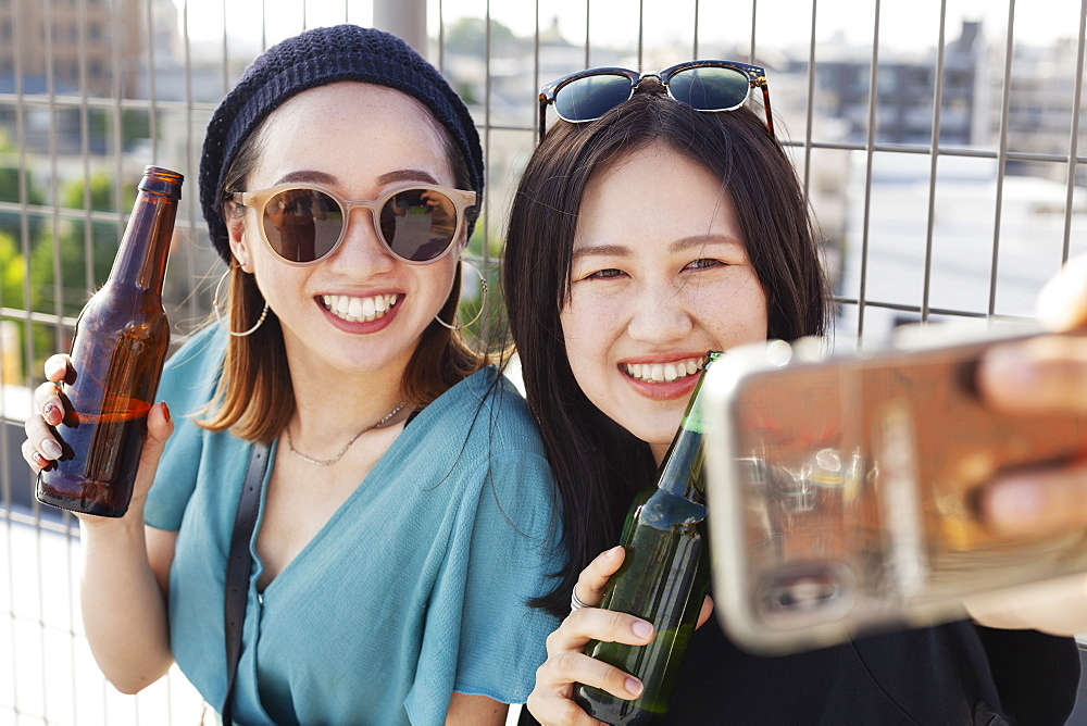 Two young Japanese women sitting on a rooftop in an urban setting, taking selfie with mobile phone, Fukuoka, Kyushu, Japan