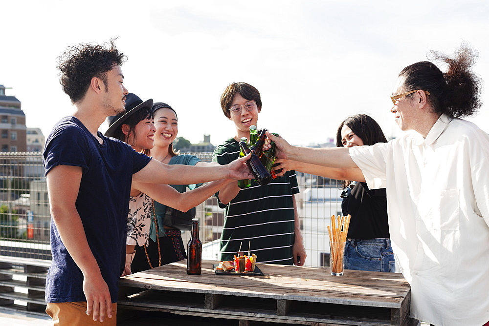 Group of young Japanese men and women standing on a rooftop in an urban setting, drinking beer, Fukuoka, Kyushu, Japan