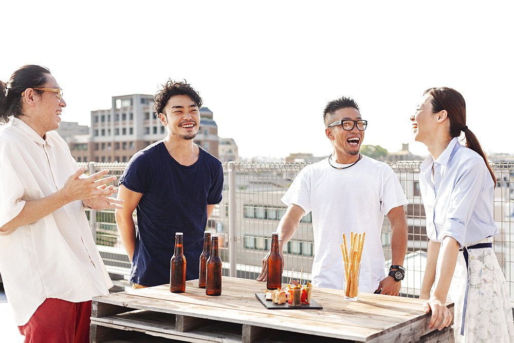 Group of young Japanese men and women standing on a rooftop in an urban setting, drinking beer, Kyushu, Japan