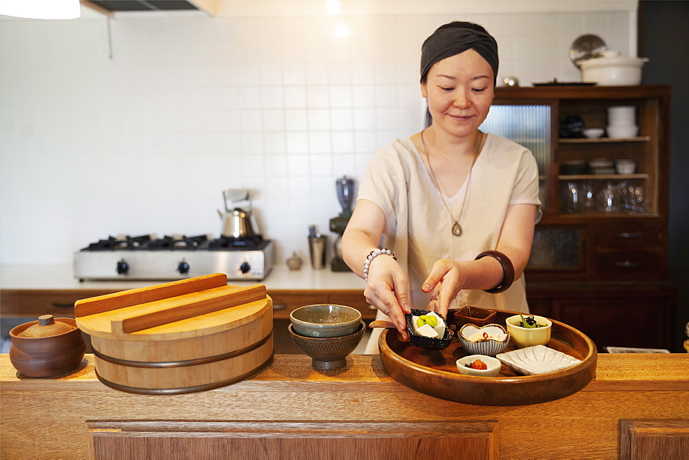 Japanese woman preparing food in a vegetarian cafe, Kyushu, Japan