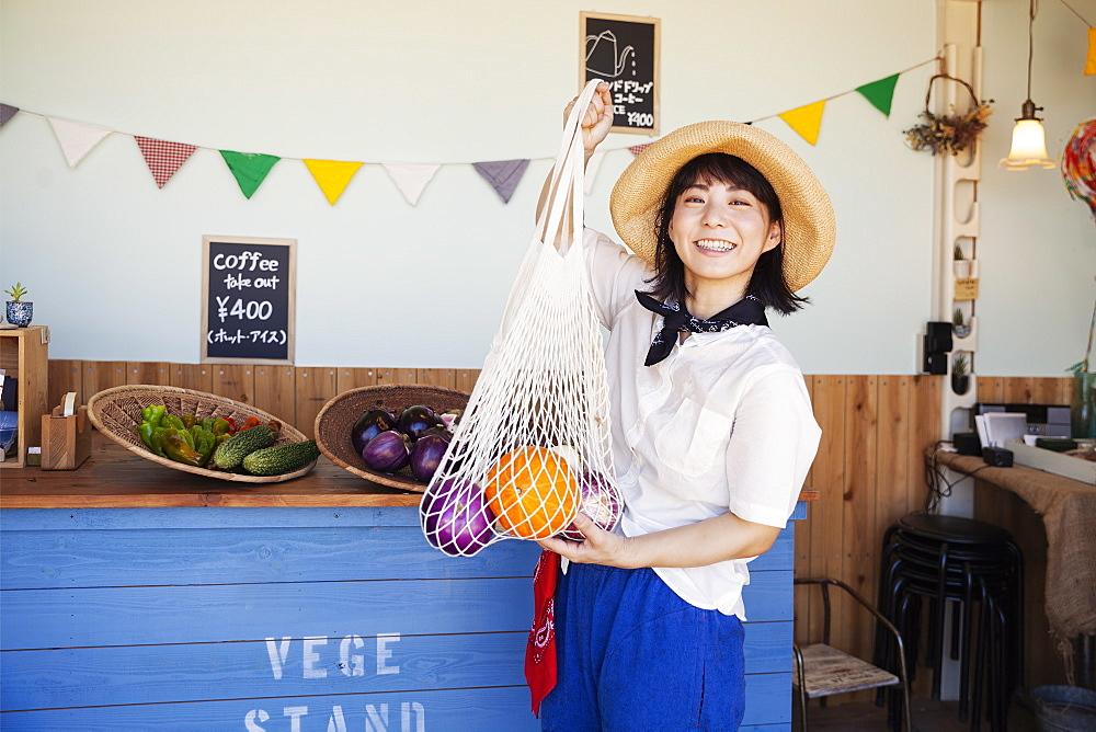 Japanese woman wearing hat working in a farm shop, smiling at camera, Kyushu, Japan