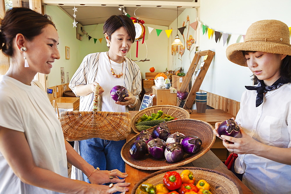 Japanese woman wearing hat working in a farm shop, serving two female customers, Kyushu, Japan