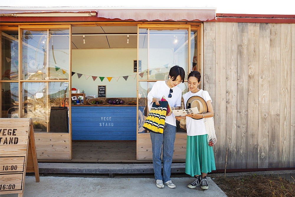 Two smiling Japanese women standing outside a farm shop, Kyushu, Japan
